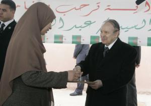 Algeria's President Abdelaziz Bouteflika gives a key to a