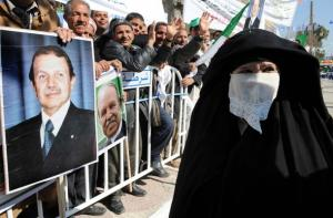 An Algerian woman passes by supporters carrying portraits of President