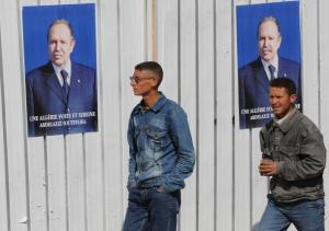Algerian men walk past electoral posters of President Abdelaziz Bouteflika