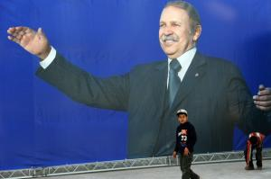 Algerian children walk next to a huge electoral poster of