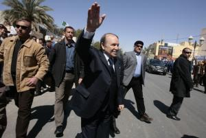 Algeria's President Abdelaziz Bouteflika (C) greets supporters while flanked by