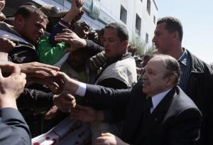 Algeria's President Abdelaziz Bouteflika (R) shakes hands with supporters as