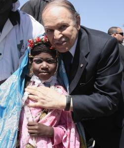 Algeria's President Abdelaziz Bouteflika (R) poses with a girl dressed