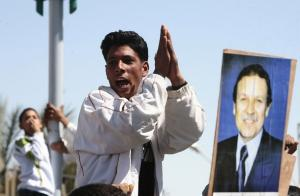 A supporter cheers for Algeria's President Abdelaziz Bouteflika (pictured on
