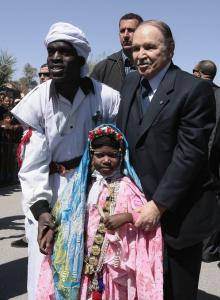 Algeria's President Abdelaziz Bouteflika (R) poses with people dressed in