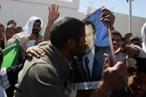 A supporter kisses a poster of Algeria's President Abdelaziz Bouteflika