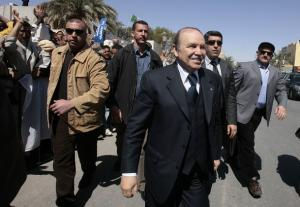 Algeria's President Abdelaziz Bouteflika (C) walks while flanked by his