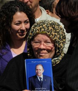 An Algerian woman holds up a poster of President Abdelaziz