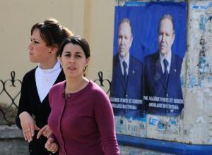 Algerian girls walk past posters of President Abdelaziz Bouteflika during