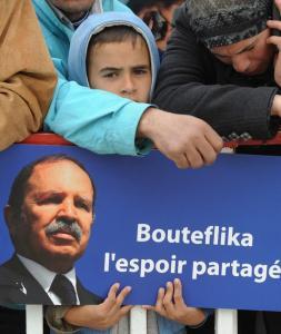 An Algerian boy carries a poster of President Abdelaziz Bouteflika