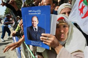 An Algerian woman holds up a poster of President Abdelaziz