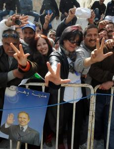 Algerians flash the V-sign for victory in support of President