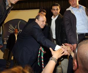 Algerian President Abdelaziz Bouteflika (C) shakes hands with supporters during
