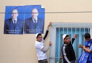 Algerian men stand underneath posters of President Abdelaziz Bouteflika during