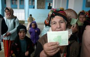 A Kabyle woman shows her voting Identification at a polling