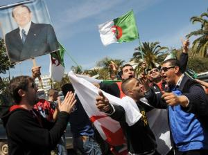 Algerians hold up placards and national flags during a gathering