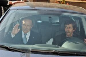 Algerian President Abdelaziz Bouteflika, left, waves as he arrives at