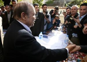 Algeria's President Abdelaziz Bouteflika shakes hands with journalists at his