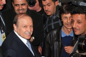 Algerian President Abdelaziz Bouteflika, foreground, arrives at his campaign headquarters