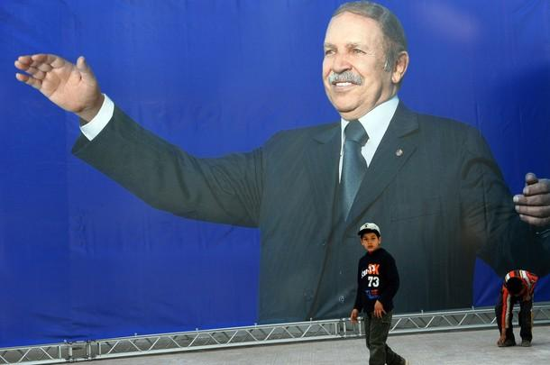 Algerian children walk next to a huge electoral poster of