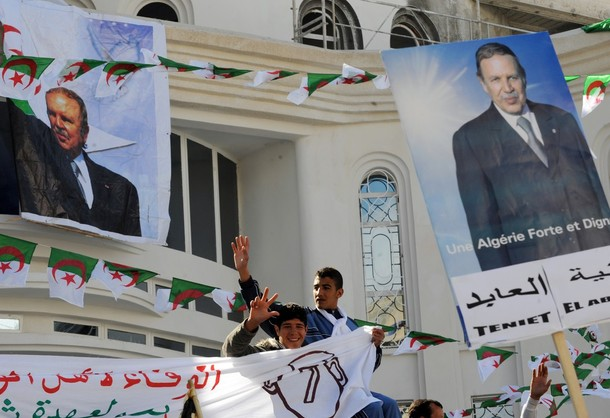Algerian youths flash the V-sign among posters portraying Algerian President