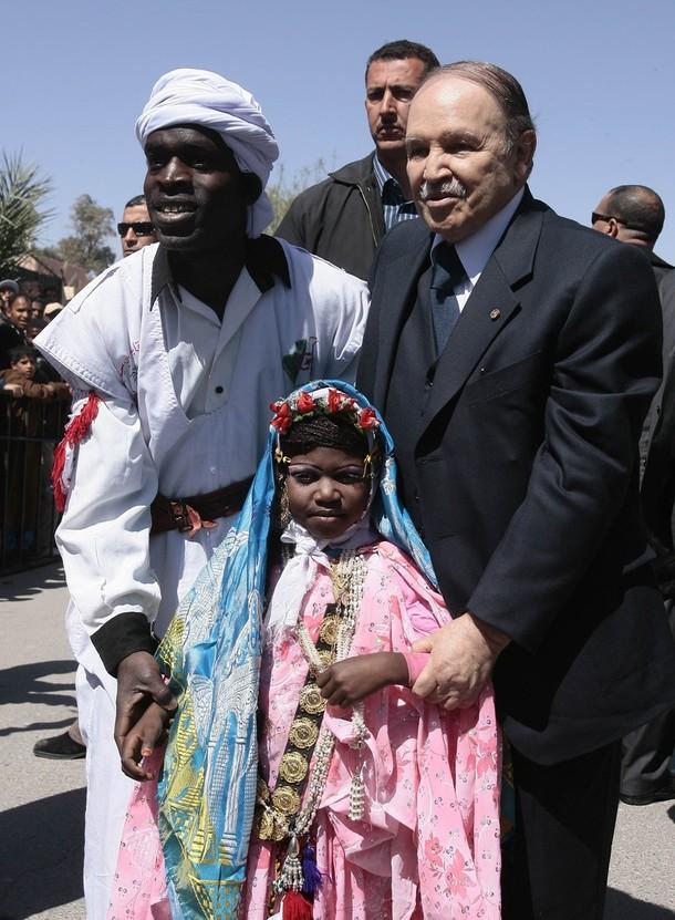 Algeria's President Abdelaziz Bouteflika (R) poses with people dressed in