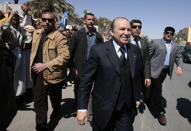 Algeria's President Abdelaziz Bouteflika (C) walks while flanked by his