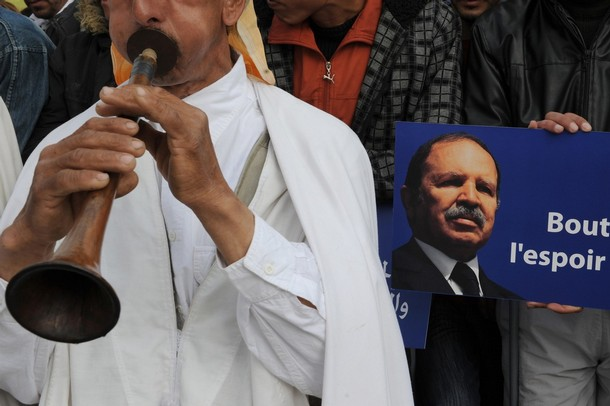 An Algerian plays music next to a poster of President