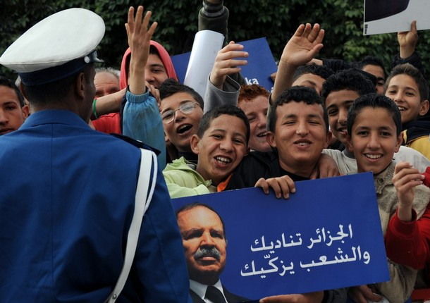 Algerian supporters carry posters of President Abdelaziz Bouteflika and shout