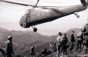 Un hélicoptère Sikorsky H-34 survole des soldats de l'armée de l'air, durant une patrouille dans le Djebel Chélial, le 12mars 1961.