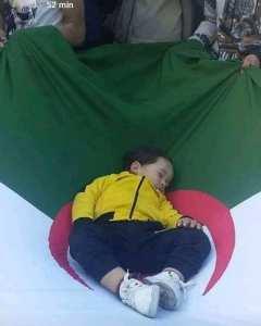 طفل نائم فوق علم الجزائر