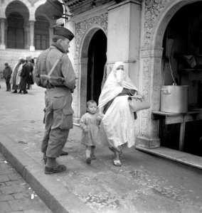 Une femme voilée et son enfant passent dans une rue d'Alger sous le regard d'un soldat français pendant la guerre d'Algérie