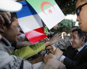 France's President Nicolas Sarkozy shakes hands with supporters as