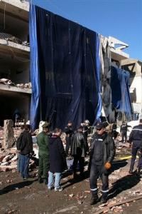 Rescuers and policemen work outside a seriously damaged building