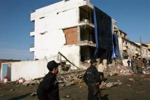 Policemen stand by the seriously damaged building of the