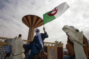 A man holds an Algerian flag as he rides