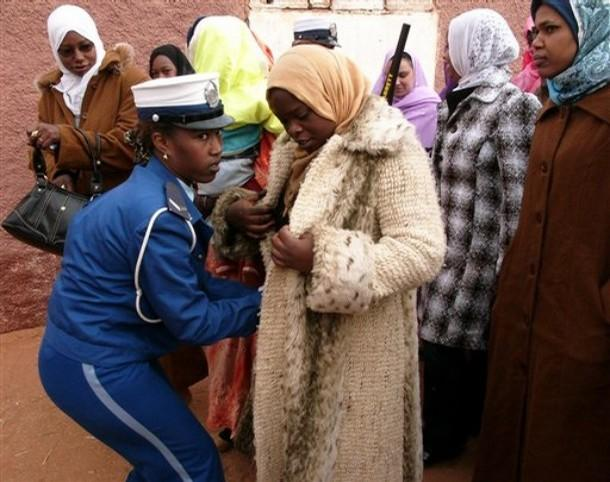 A policewoman, left, searches women wishing to attends Algerian