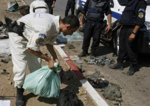 A bomb disposal expert collects evidence at the site