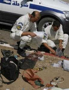 Bomb disposal experts collect evidence at the site of
