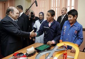 Algeria's President Abdelaziz Bouteflika (L) shakes hands with a